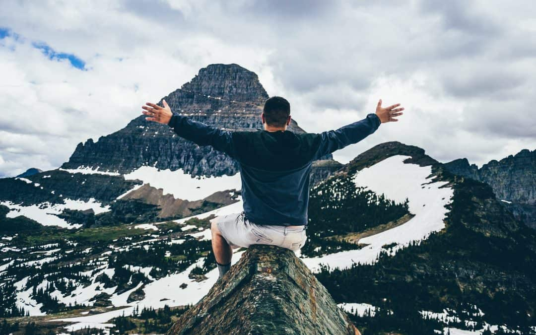 Man on top of mountain with arms open